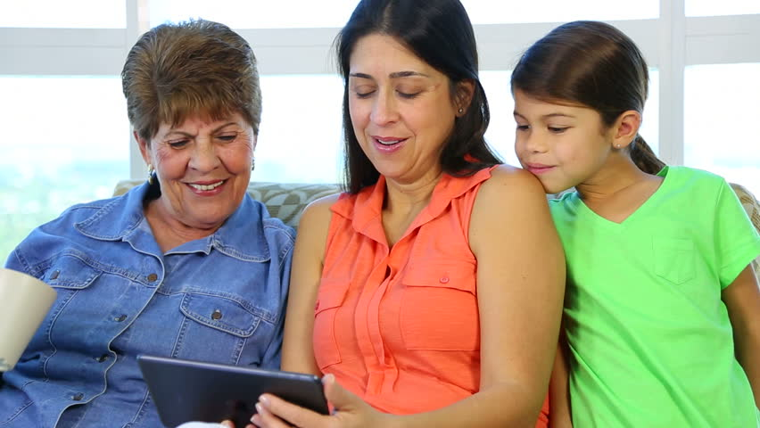 Three generations of hispanic latino females of the same family laughing while watching a tablet