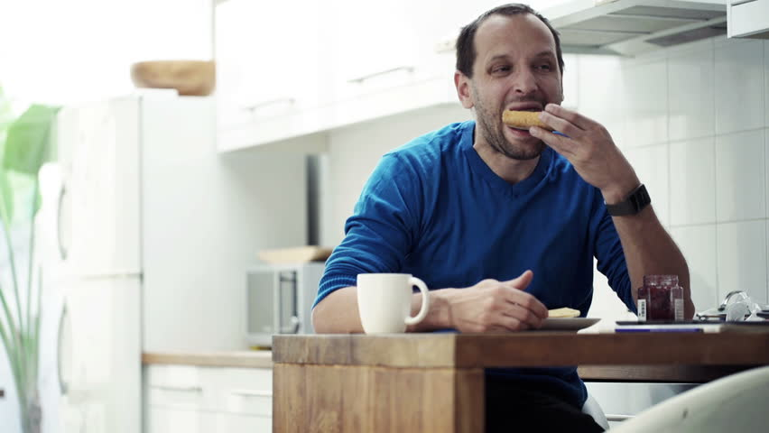 Young man preparing sandwich, eating and drinking coffee by table in kitchen