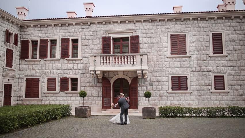 Wedding in Montenegro. Villa Milocer in Montenegro, near Sveti Stefan. Bride and groom dancing on the background of an old villa. Newlyweds honeymoon in Montenegro in spring | Shutterstock HD Video #9708269
