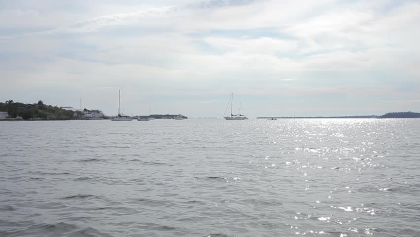 Video of sailboats resting on the water during a beautifully bright sunny day #9725891