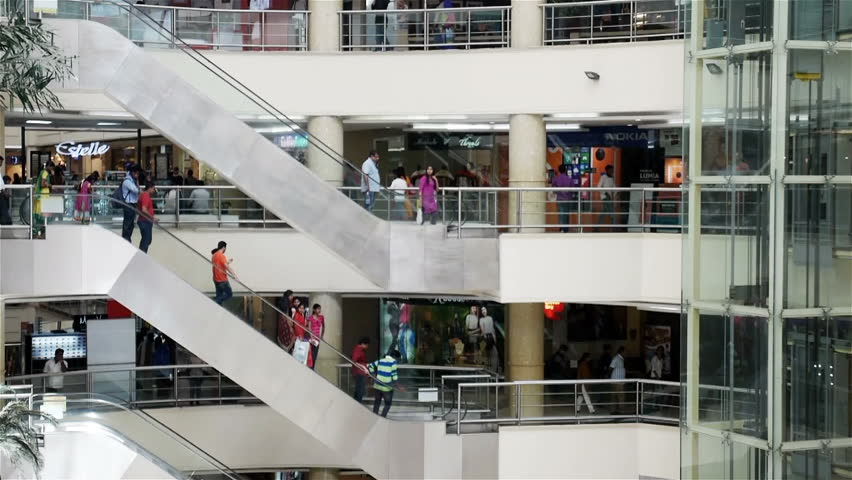 CHENNAI, INDIA - 28 MARCH 2015: Full frame video footage of a multi-storey shopping mall in Chennai, India.Local shoppers walk around and use the escalators as they indulge in retail therapy.