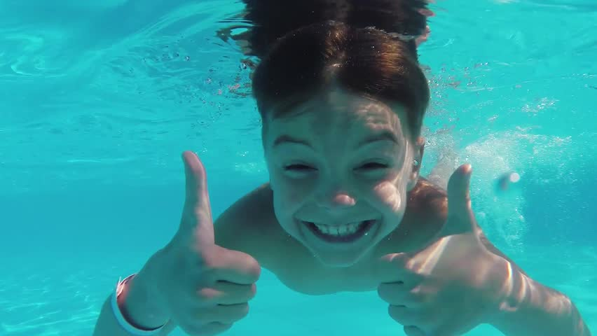 Cute teen boy dives in blue pool with open eyes - HD stock video clip