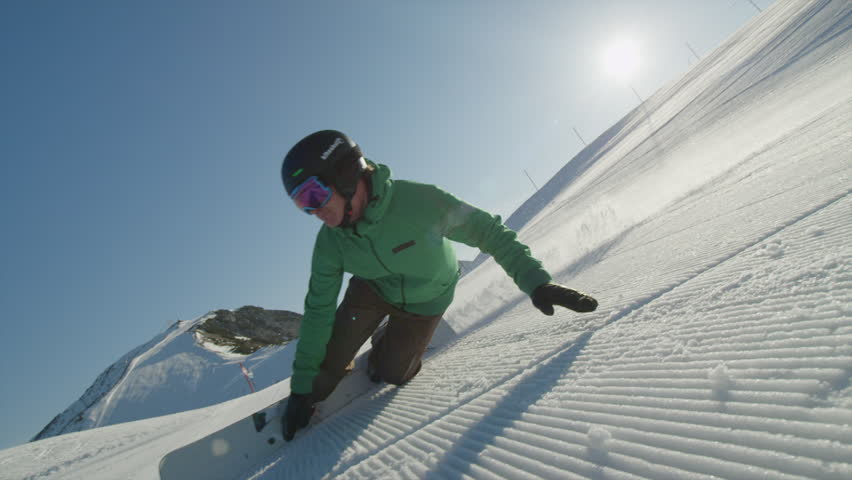 Slow motion race snowboarder riding slalom between the