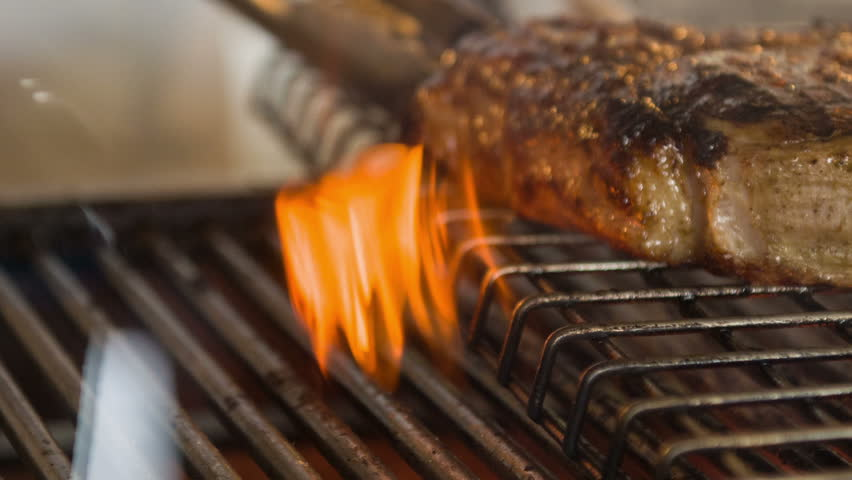 Do you want to taste. Horizontal dolly shot of wonderful soft steak lying on grill fire while chef turning it