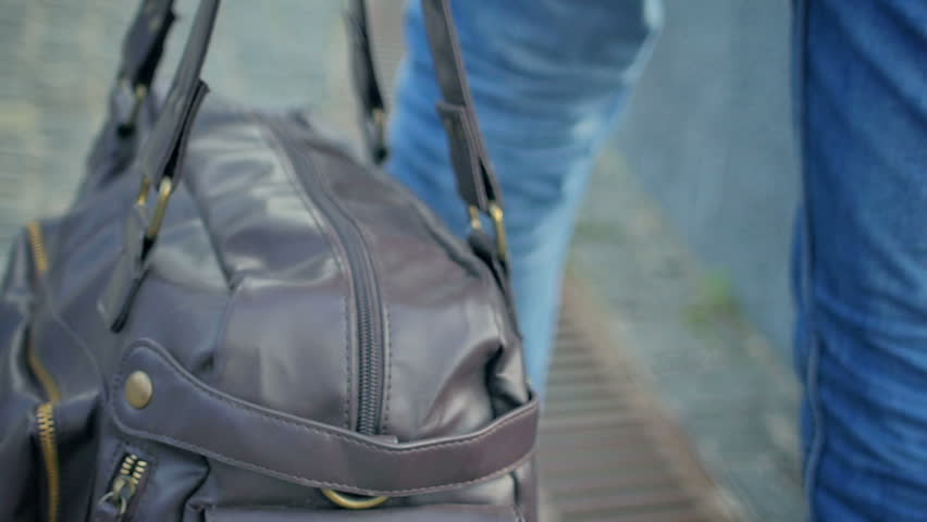 Man in jeans carries a bag. shot closeup in slow motion