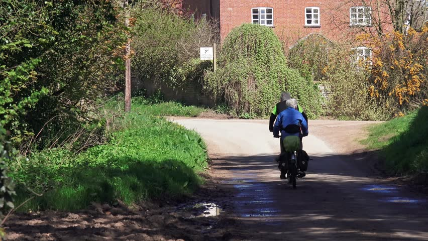 GNOSALL, STAFFORDSHIRE, ENGLAND: APRIL 27TH 2015: Elderly couple riding a tandem cycle along country lane | Shutterstock HD Video #9770576