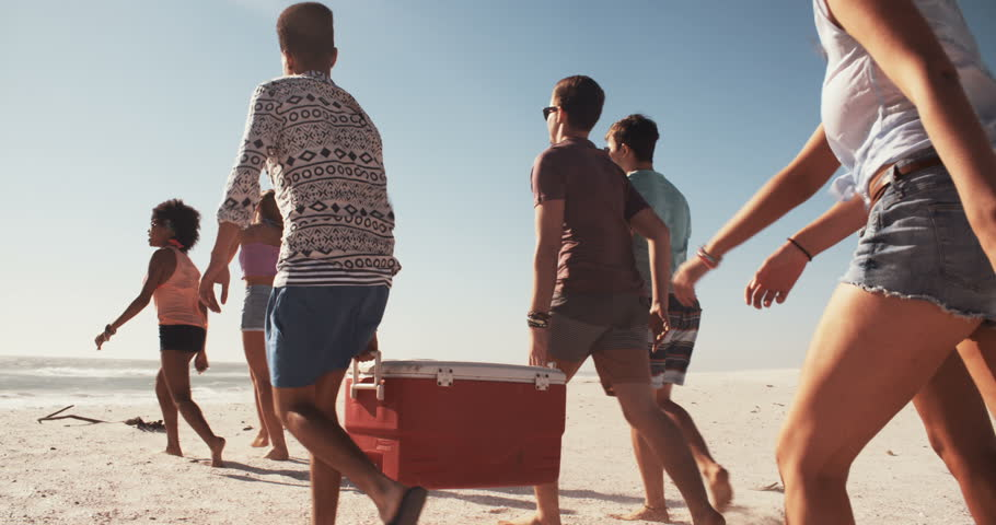 Group of friends walking on a beach and carrying a cooler box full of drinks for a party, panning in slow motion