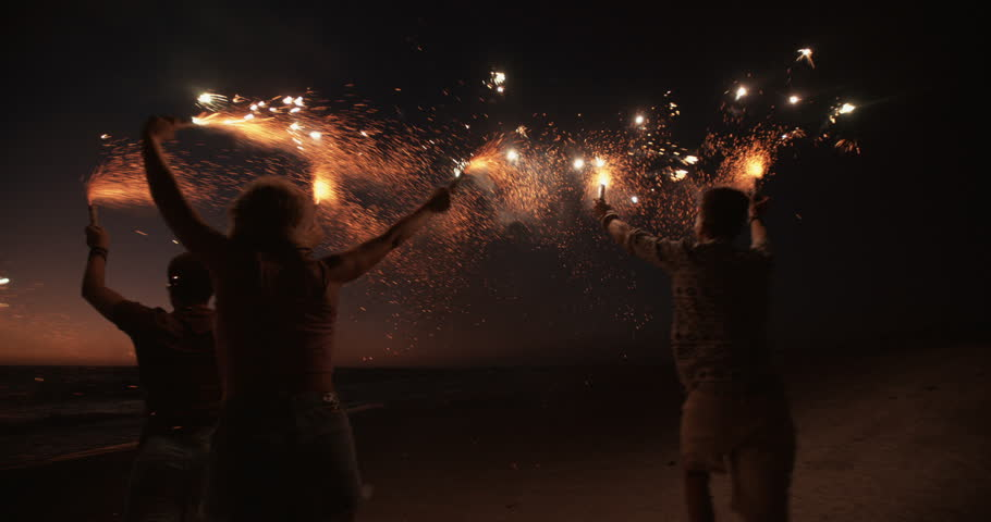 Rearview of friends running together on a beach holding sparkling fireworks in Slow Motion #9774770