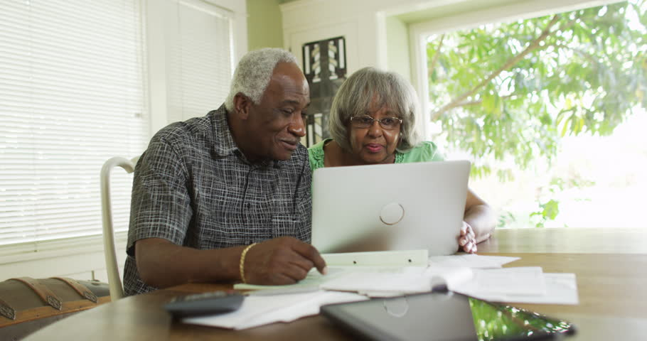 Happy mature black couple paying off bills on laptop