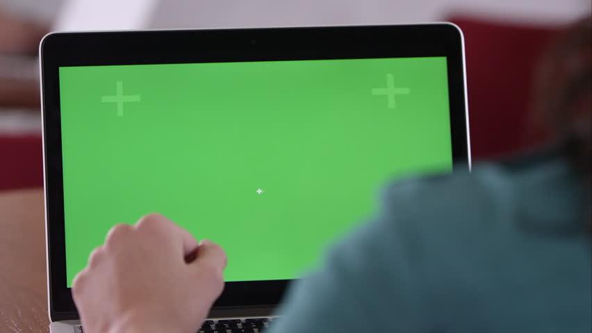 Panning shot of woman using computer with green screen.   Shutterstock HD Video #9802940