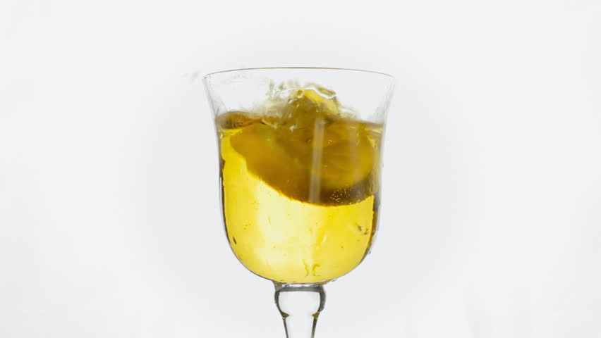 Filling a glass with fresh beer and putting a way too big slice of lemon into it. Some of the liquid splashes out of the cocktail mug. White background. - HD stock footage clip