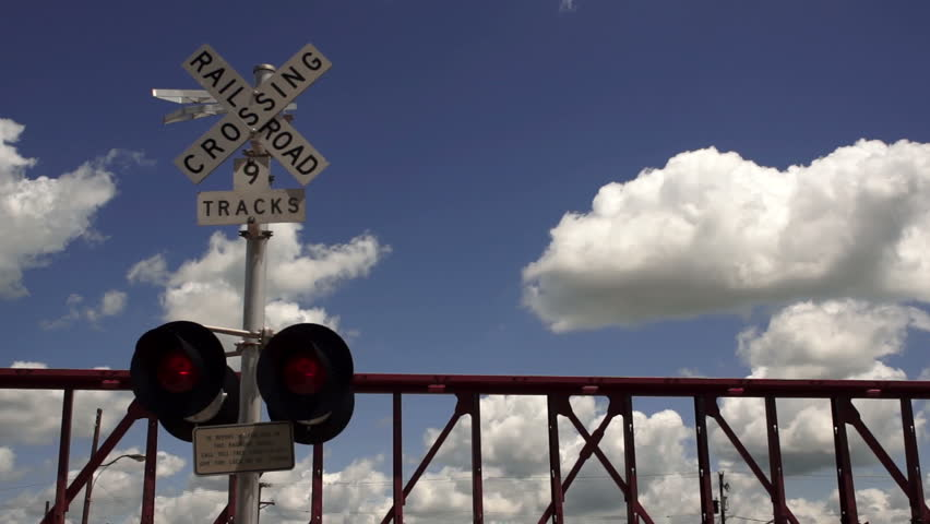 Train Passing Railroad Crossing Warning Lights Flashing Fluffy Clouds Rolling By - HD stock video clip