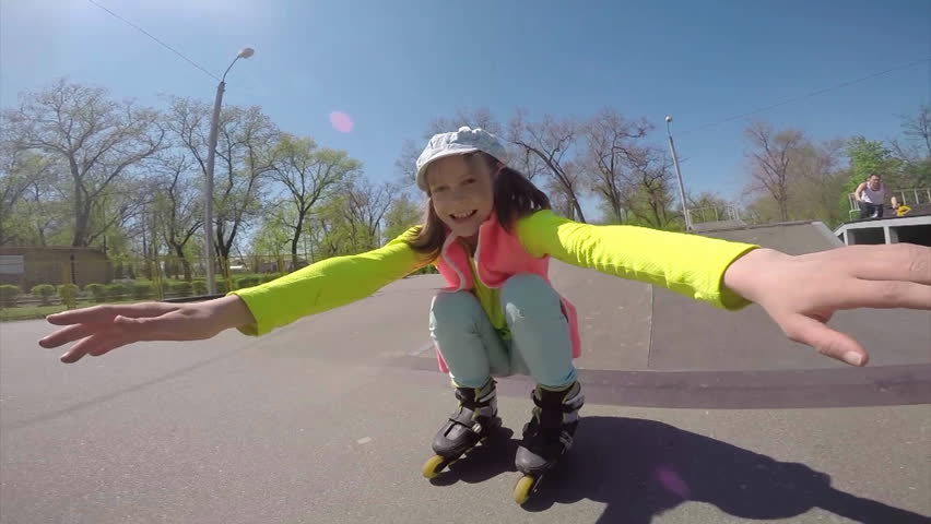Outdoor portrait of a sportive child inline skates blading in the park. Slow motion. Childhood, sports, active lifestyle concept. - HD stock footage clip