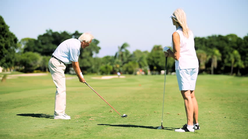 Retired senior couple enjoying a healthy outdoor lifestyle playing golf - HD stock footage clip