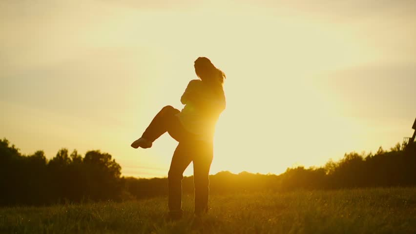 Romantic young couple silhouette. Man is holding a woman on his hands and spinning around on a sunset with the sun shining. Slow motion filmed at 240 fps.. - HD stock footage clip