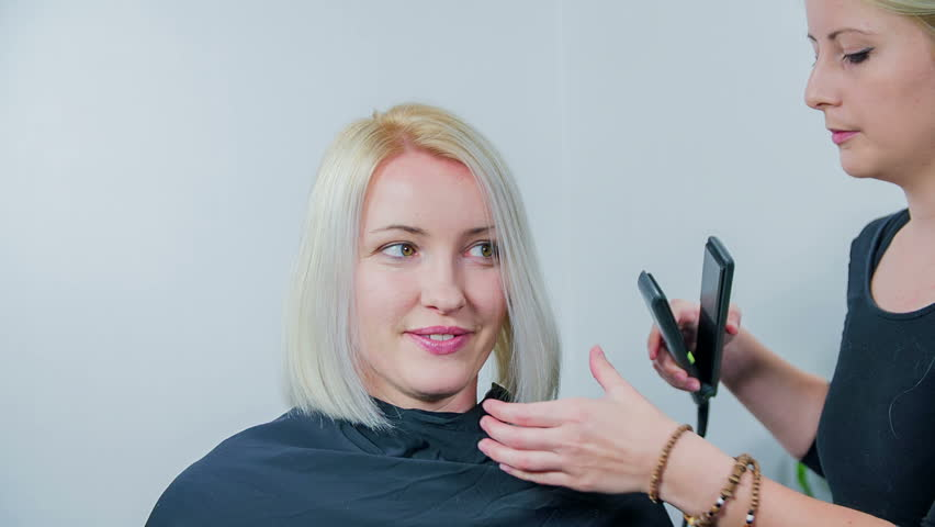 Hair dresser is ironing costumers hair . Slow motion total RAW footage of a young hair dresser ironing the woman hair who is seating on the cheer. | Shutterstock HD Video #9843881