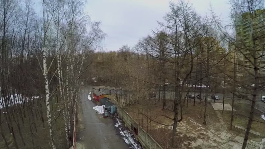 City outskirts with garages and road near national park on Elk island in Moscow at spring cloudy day. Aerial view - HD stock footage clip