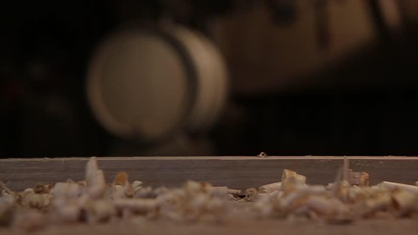 Man hands with carpenters plane production of oak barrels.