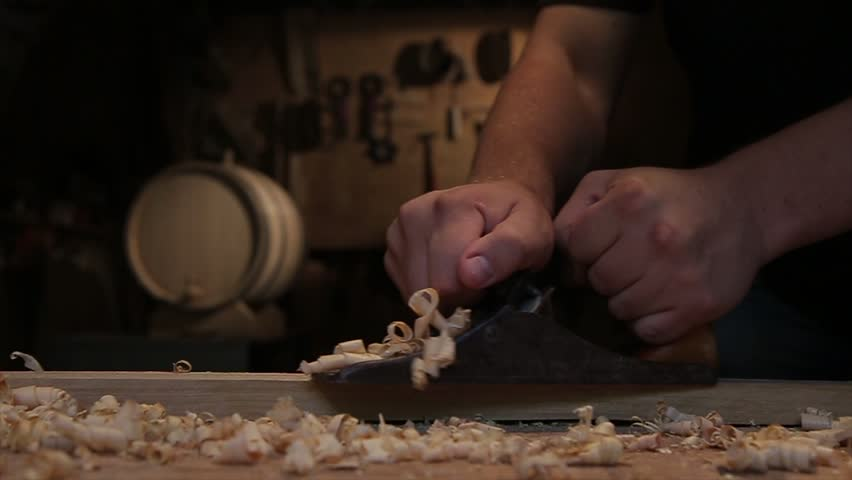 Man hands with carpenters plane production of oak barrels.