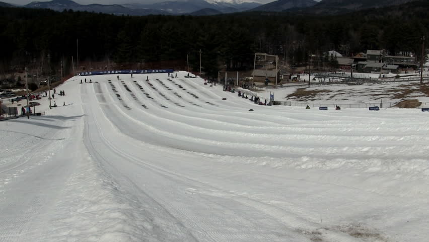 Looking down from top of snow tubing trails as tubers make their way down twisting and turning. | Shutterstock HD Video #9924854