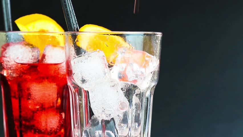 barman pouring red spritz aperitif aperol cocktail with two orange slices and ice cubes on black background - HD stock footage clip