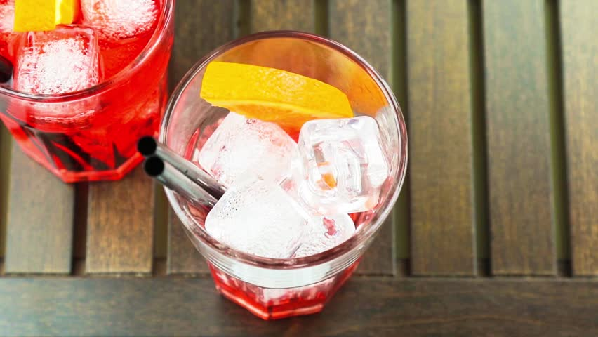 top of view of pouring red spritz aperitif aperol cocktail with orange slices and ice cubes on wood table - HD stock video clip