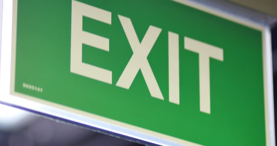 An exit sign footage, the shot moves from the top to the bottom