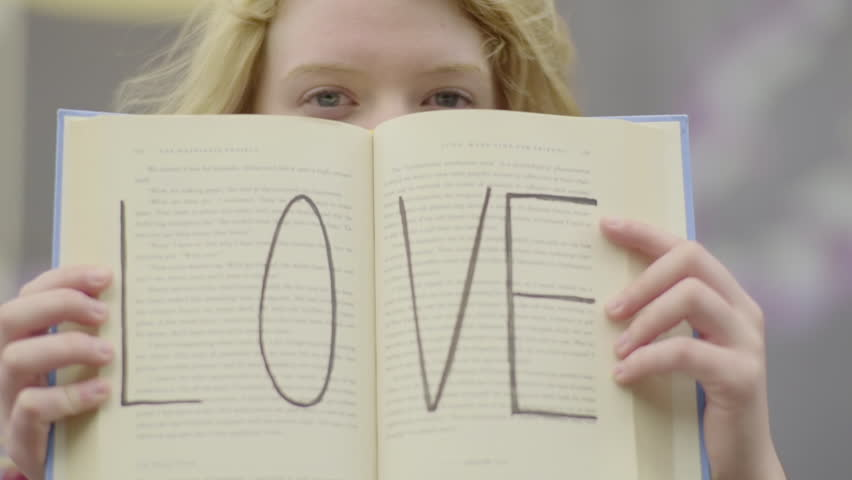 Girl Holds Book Open, In Front Of Her Face, It Says LOVE On The Pages (Slow Motion)