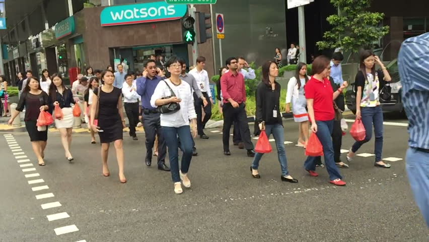 SINGAPORE CITY/SINGAPORE - JANUARY 11, 2015: Slow motion as unidentified business people walk across the street. People of Chinese extraction form 74.2% of the population. - HD stock footage clip