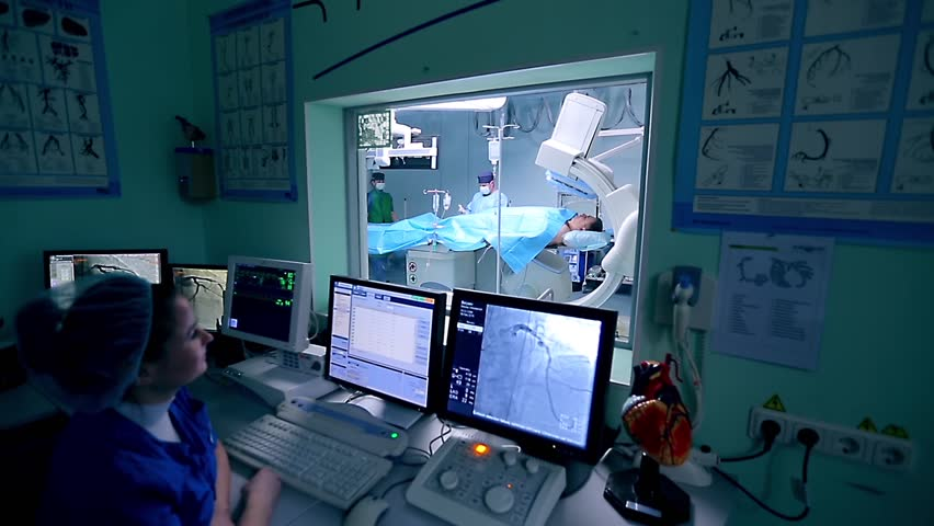 Assistant controls a cardio surgery in front of monitors in a control room. In an operation room a surgeon makes manipulations with a patient.