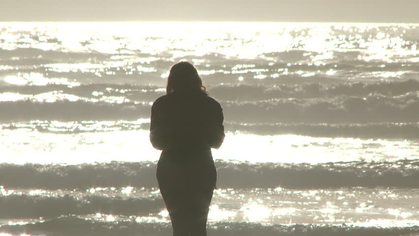 Woman stands at the Pacific Ocean in Oregon on sunny day by herself.