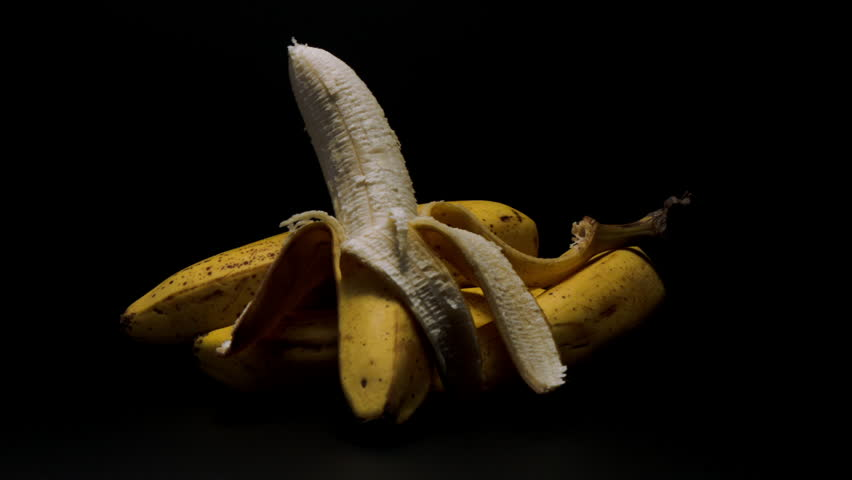 FOUR BANANAS, ONE IS HALF NAKED, ON A DRAMATIC, MATTE BLACK BACKGROUND. HIGH CONTRAST SHOT. - HD stock footage clip